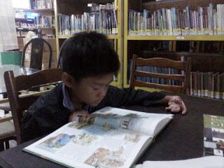 Seorang anak sedang asyik membaca buku ensiklopedia bergambar dengan tema flora dan fauna