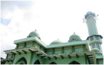 Masjid Zending berwarna hijau muda. Di belakang masjid ada sebuah asrama santri dua lantai