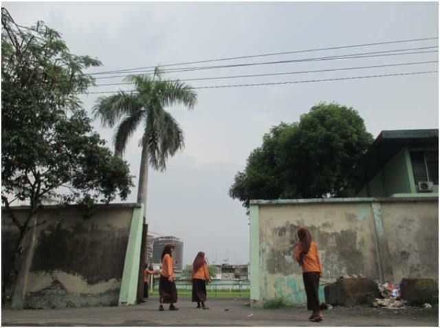 Anak-anak sekolah berseragam Pramuka bermain dan bercanda di Stadion Kebun Bunga Medan