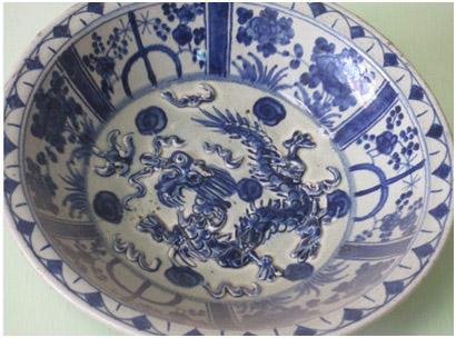 Piring biru bermotif naga timbul. Di pasaran barang antik, piring ini bernilai mahal