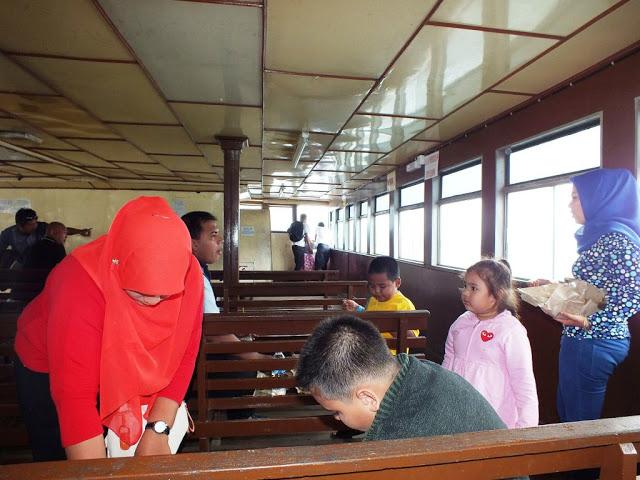 Menikmati bekal makanan di ruangan penumpang kapal ferry